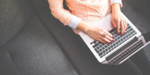 A woman in an orange shirt sat on a dark grey sofa typing on an Apple Mac laptop